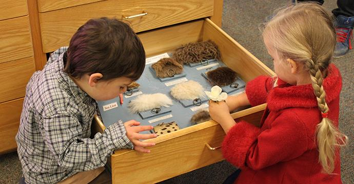 Photo of two children interacting with an exhibit on fur