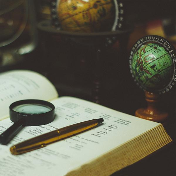 Photo of a magnifying glass and a pen atop a textbook. A globe is in the background