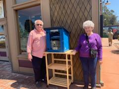 Philip and Manette Gerstle posing next to the little free library stand out in front of the Museum